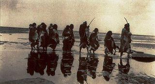 Familia selk'nam caminando en una playa.